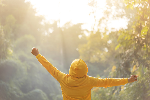 Happy woman traveler in yellow sweater with hood is standing with raised arms.