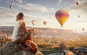 istock Happy woman traveler watching the hot air balloons at the hill of Cappadocia, Turkey. 1164258102