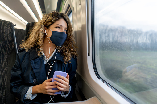 Happy woman traveling by train wearing a facemask during the COVID-19 pandemic and listening to music with headphones while looking at the window view