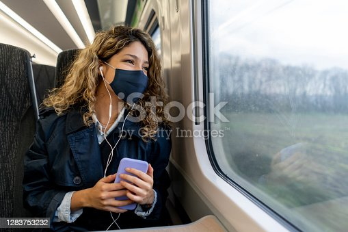 istock Happy woman traveling by train wearing a facemask 1283753232