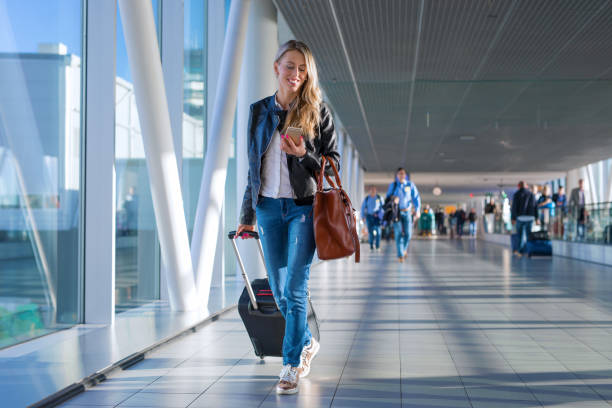 Happy woman travelling and walking in airport stock photo