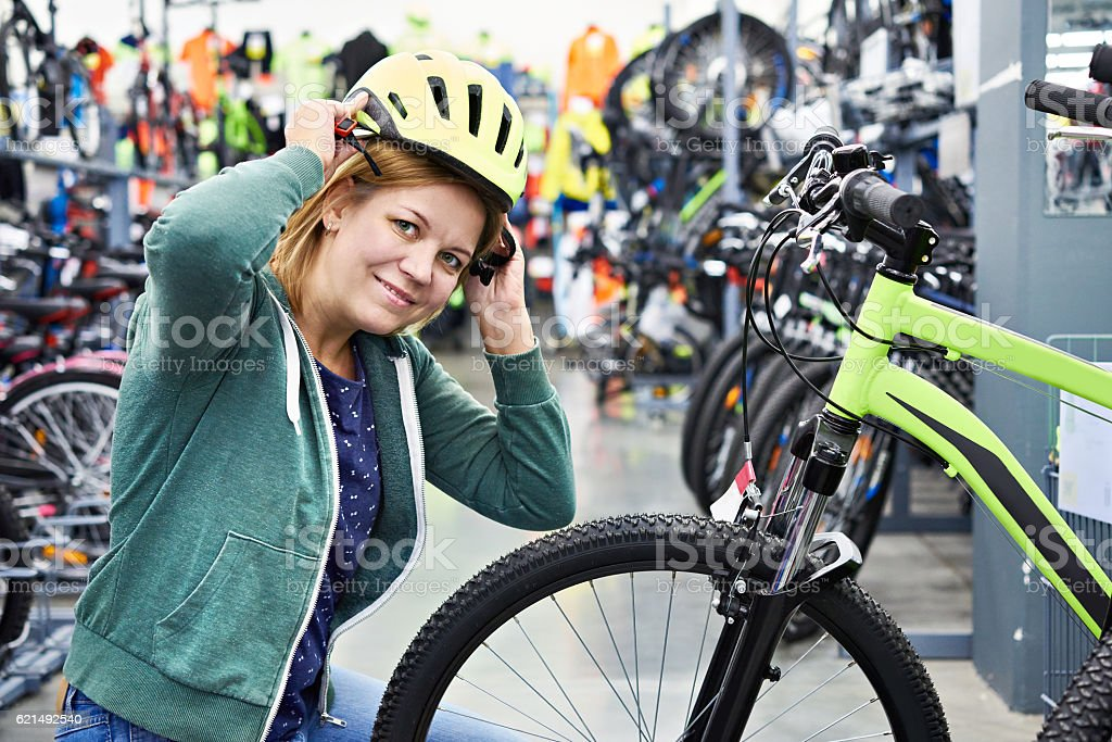 Happy woman trying helmet for cycling in store photo libre de droits