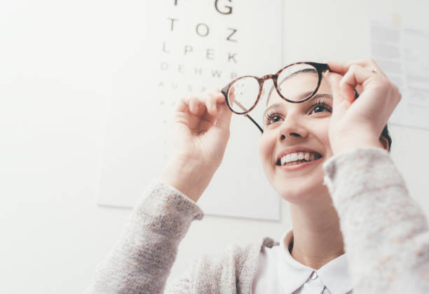 Happy woman trying her new glasses stock photo