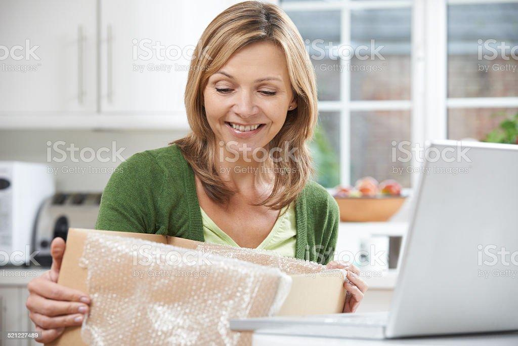 Happy Woman Unpacking Online Purchase At Home stock photo