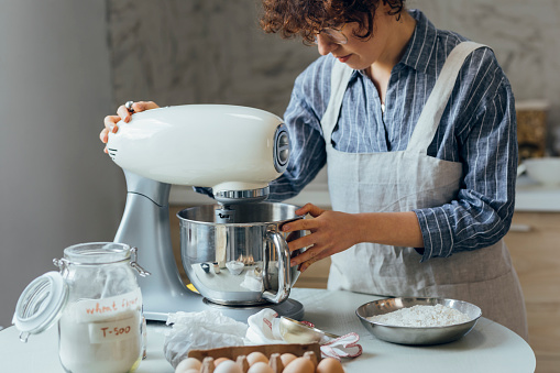 Woman in an apron mixing cookie dough in the kitchen.