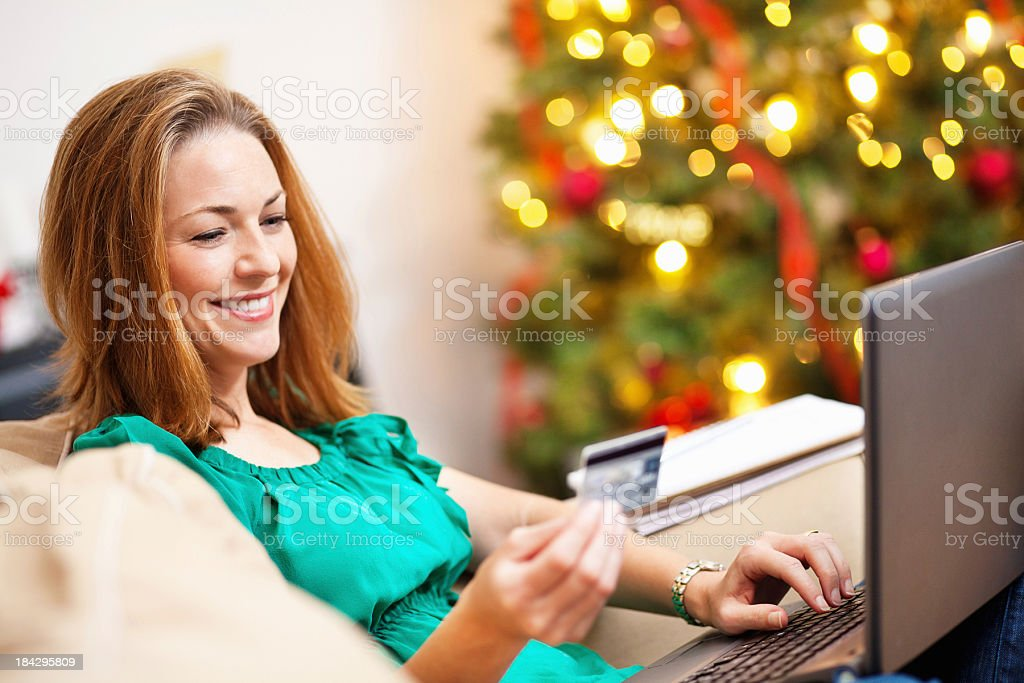 Happy Woman Using Credit Card While Doing Christmas Shopping Online royalty-free stock photo
