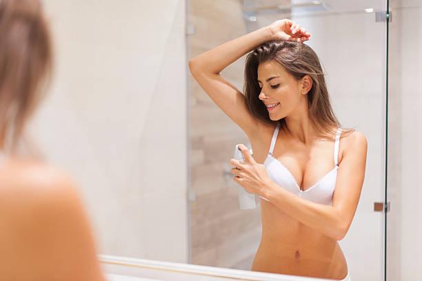 glückliche frau mit deodorant am unterarm - feminine badezimmer stock-fotos und bilder