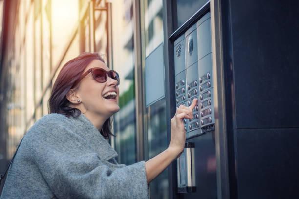 happy woman using intercom at building entrance. - squillare foto e immagini stock