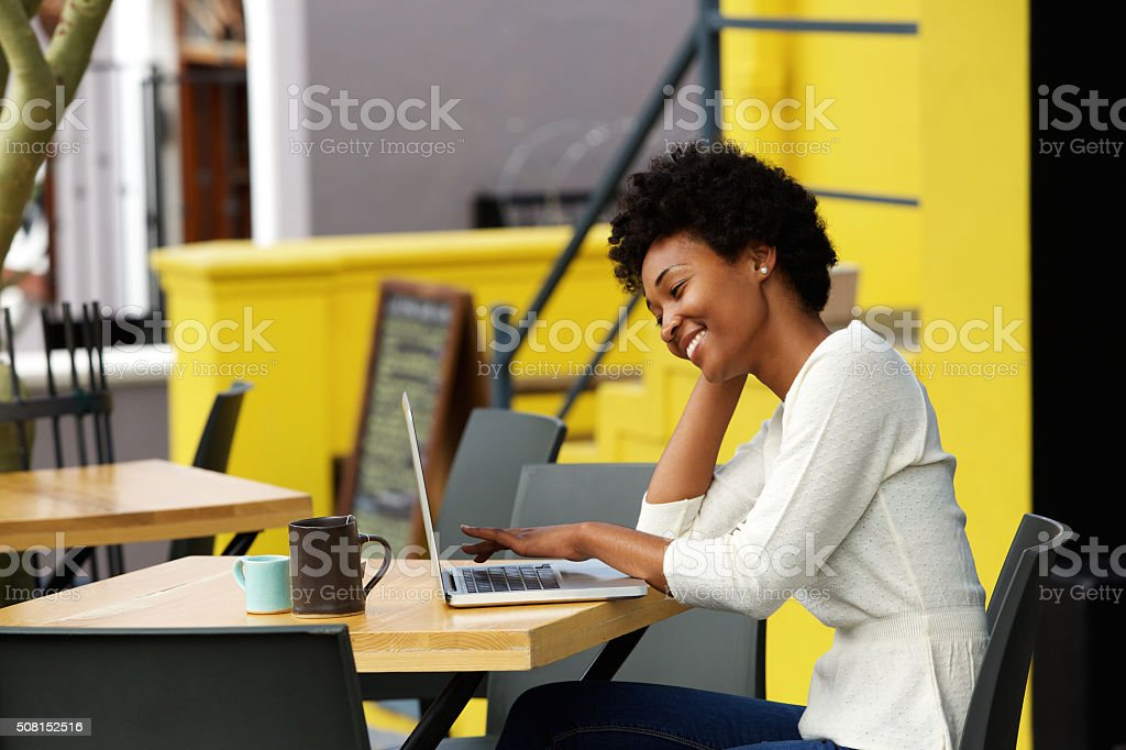 Happy woman using laptop at cafe stock photo