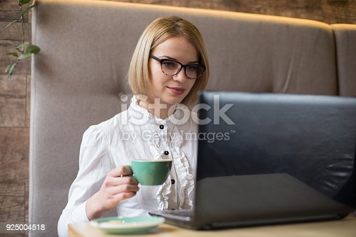 istock Happy woman using laptop at cafe. Young beautiful girl sitting in a coffee shop and working on computer 925004518
