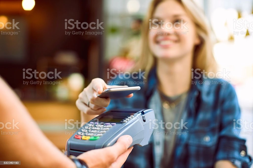 Happy woman using mobile payment at coffee shop stock photo