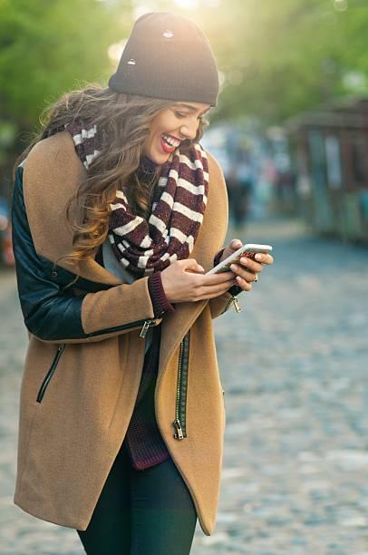 happy woman using mobile phone, - winterjacke lang damen stock-fotos und bilder