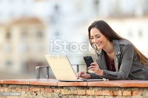 istock Happy woman using phone and laptop in a balcony 1077193980