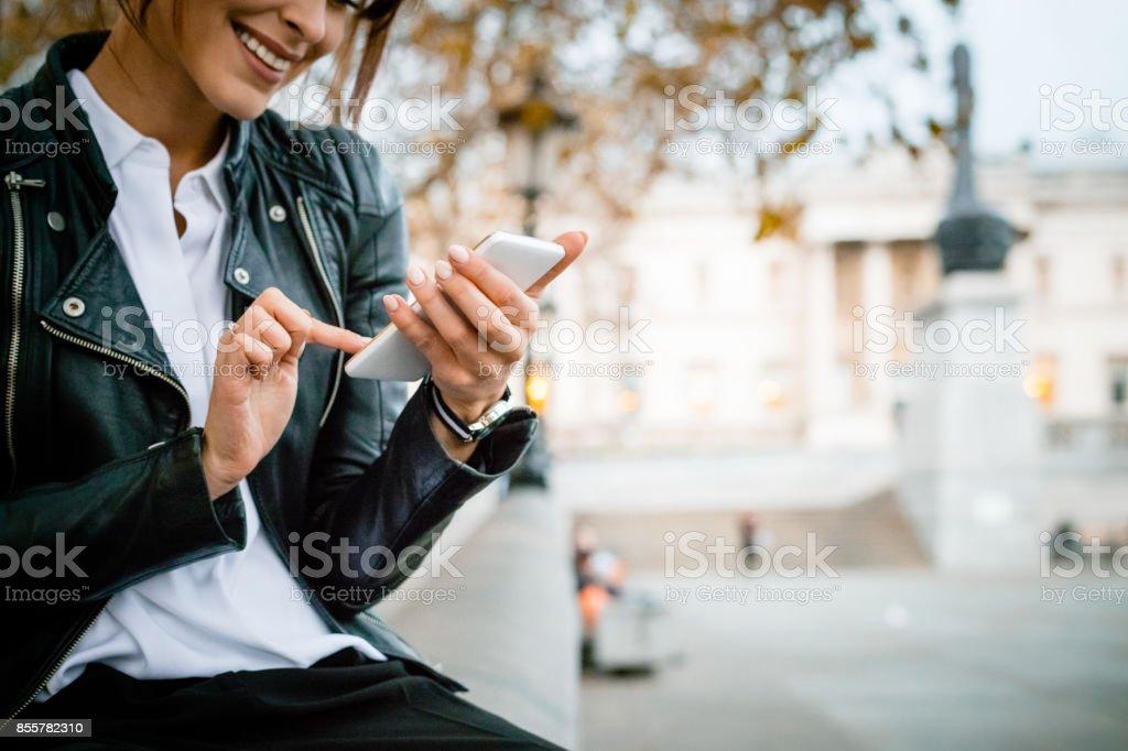Happy woman using smart phone at Trafalgar Square in London, autumn season - Foto stock royalty-free di Adulto