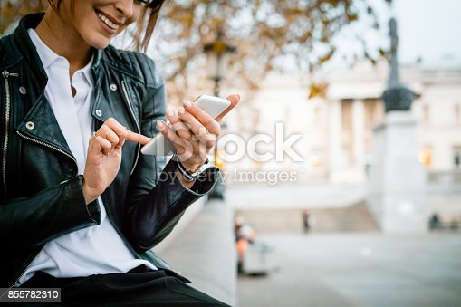 Beautiful, happy woman wearing leather jacket sitting at Trafalgar Square in London and using smart phone. Autumn season. National Gallery in the background. Close up of hands.