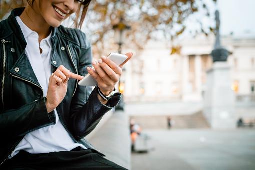 Happy Woman Using Smart Phone At Trafalgar Square In London Autumn Season - Fotografie stock e altre immagini di Adulto