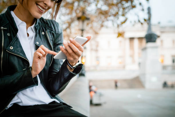 happy woman using smart phone at trafalgar square in london, autumn season - woman smartphone stock photos and pictures