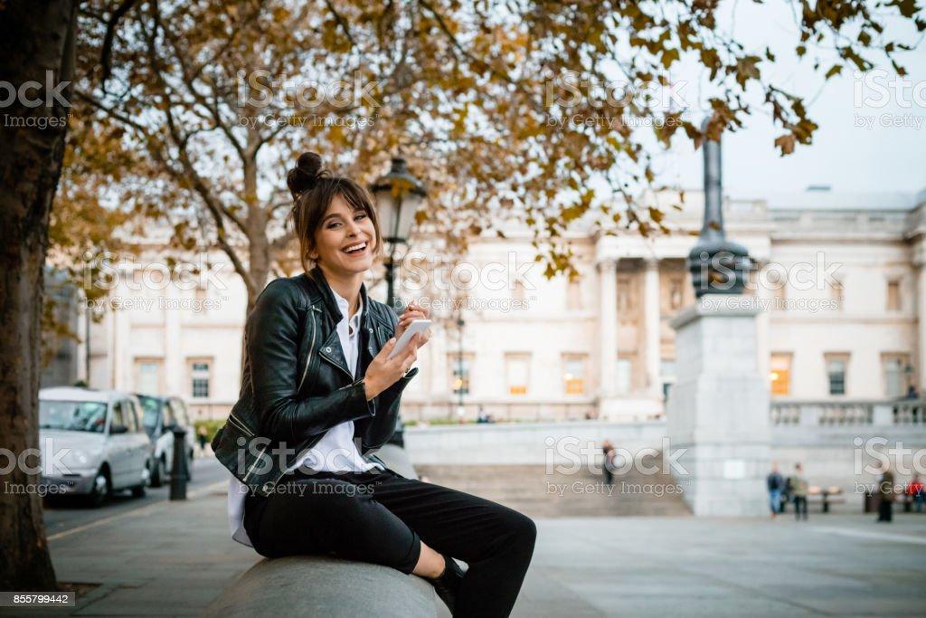 Glückliche Frau mit Smartphone am Trafalgar Square in London, Herbstsaison – Foto