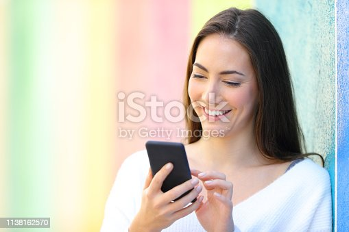 istock Happy woman using smart phone in a colorful wall 1138162570