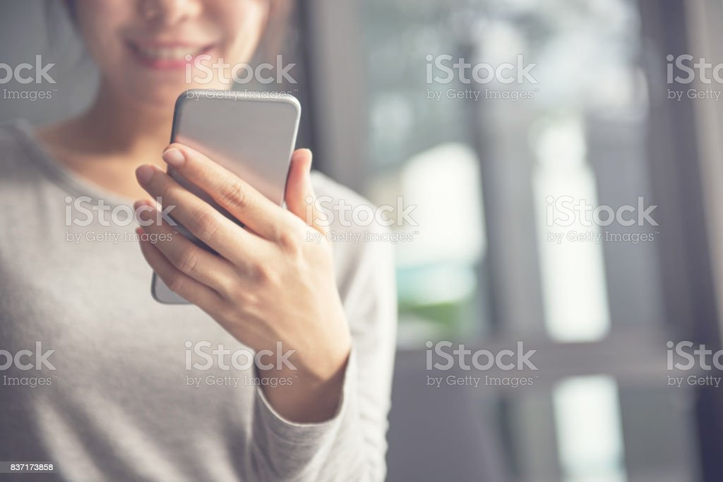 Happy woman using smartphone and copy space stock photo