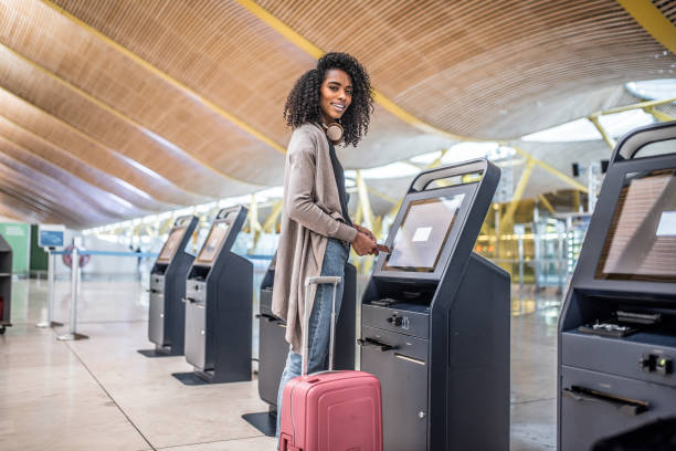 happy woman using the check-in machine at the airport getting the boarding pass. stock photo