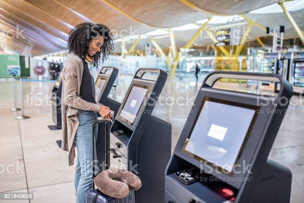 Happy woman using the checkin machine at the airport getting the picture id821840636?b=1&k=6&m=821840636&s=612x612&h=jvz6duk slzxnyeyvrgbx0qcbci6mtwproe3zzgge5g=