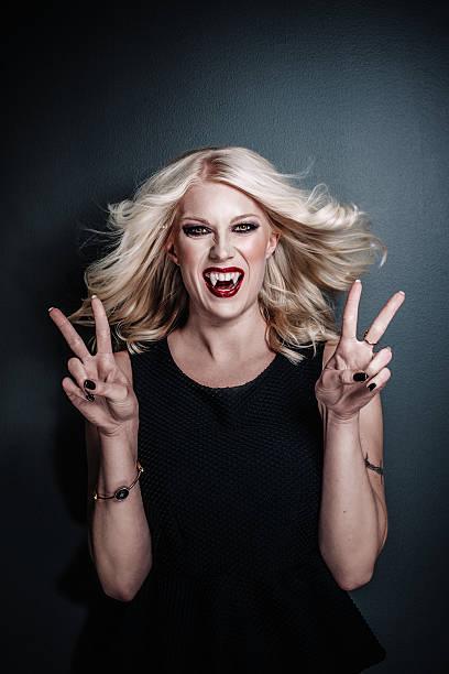 glückliche frau vampir macht victory-zeichen - bestes halloween make up stock-fotos und bilder