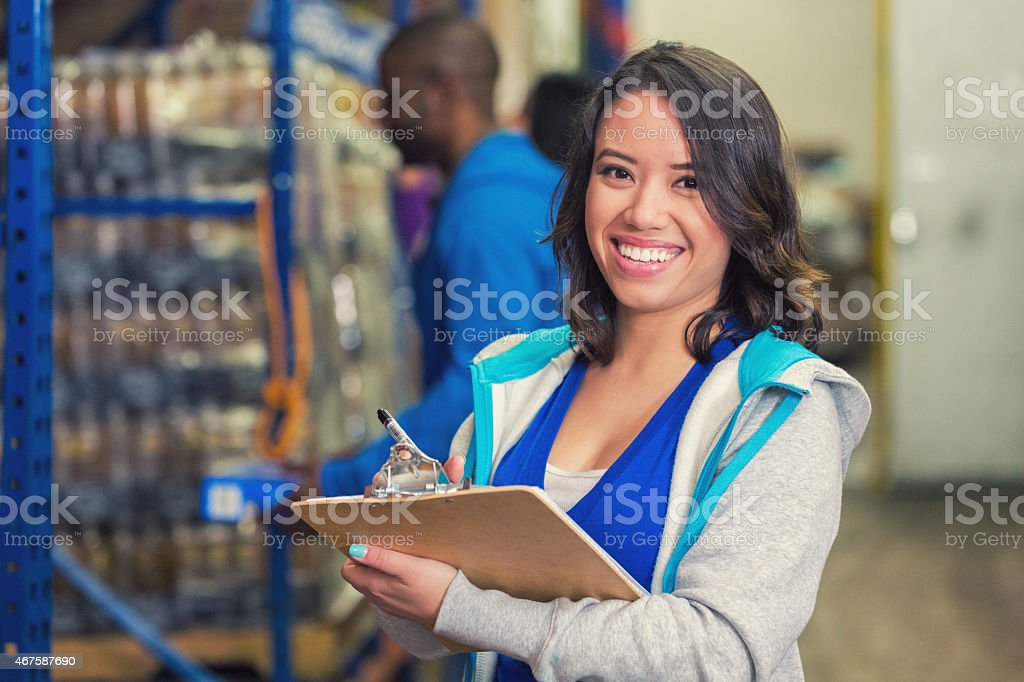 Happy woman volunteering in charity food bank warehouse, taking inventory stock photo