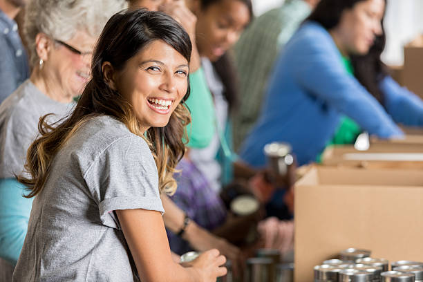 happy woman volunteers at a food bank - charity and relief work - fotografias e filmes do acervo