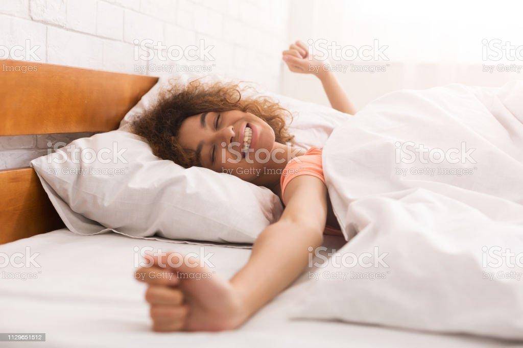 Glückliche Frau aufwachen nach Schlaf auf Bett - Lizenzfrei Abenddämmerung Stock-Foto