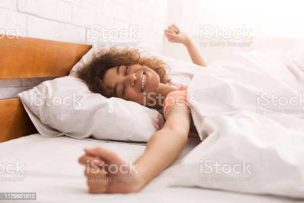 Glückliche Frau Aufwachen Nach Schlaf Auf Bett Stockfoto und mehr Bilder von Abenddämmerung