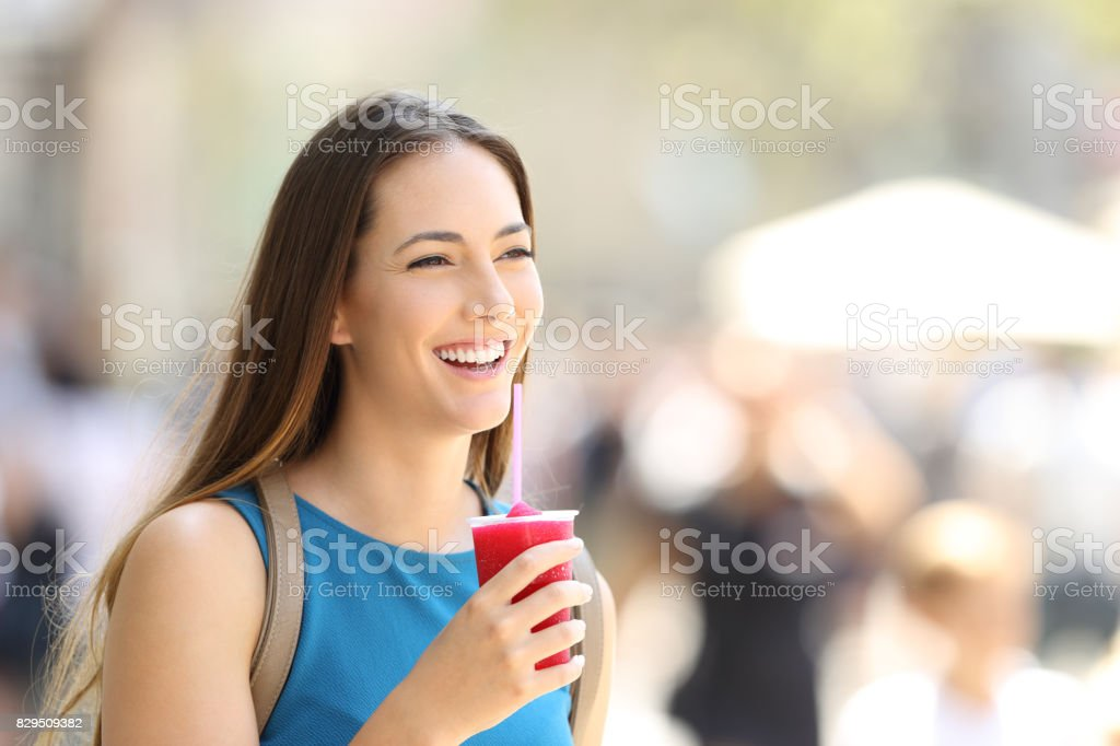Happy woman walking and holding a slush stock photo