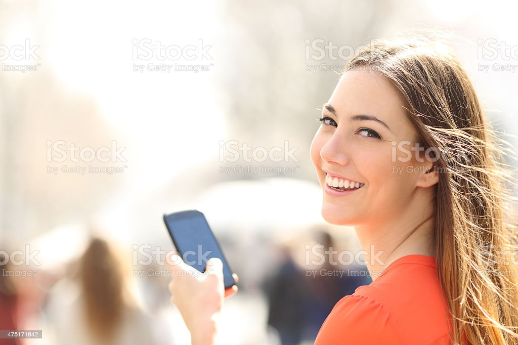 Happy woman walking in the street using a smartphone stock photo