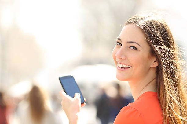 Feliz mulher andando na rua usando um smartphone - foto de acervo