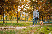 istock Happy woman walking on a park trail with a small brown dog in autumn 1191299066