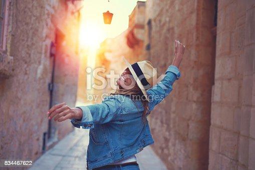 Happy woman in hat dancing on mediterreanen street in sunset