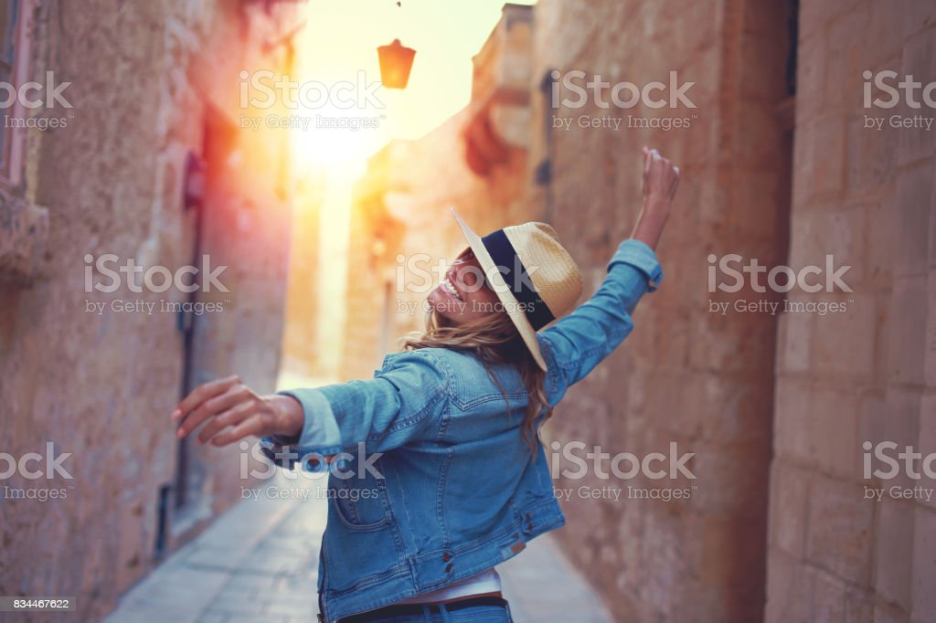 Happy woman walking on mediterreanen street in sunset stock photo