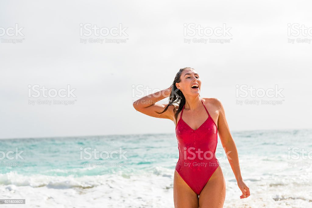 Happy Woman walking out of the sea. stock photo