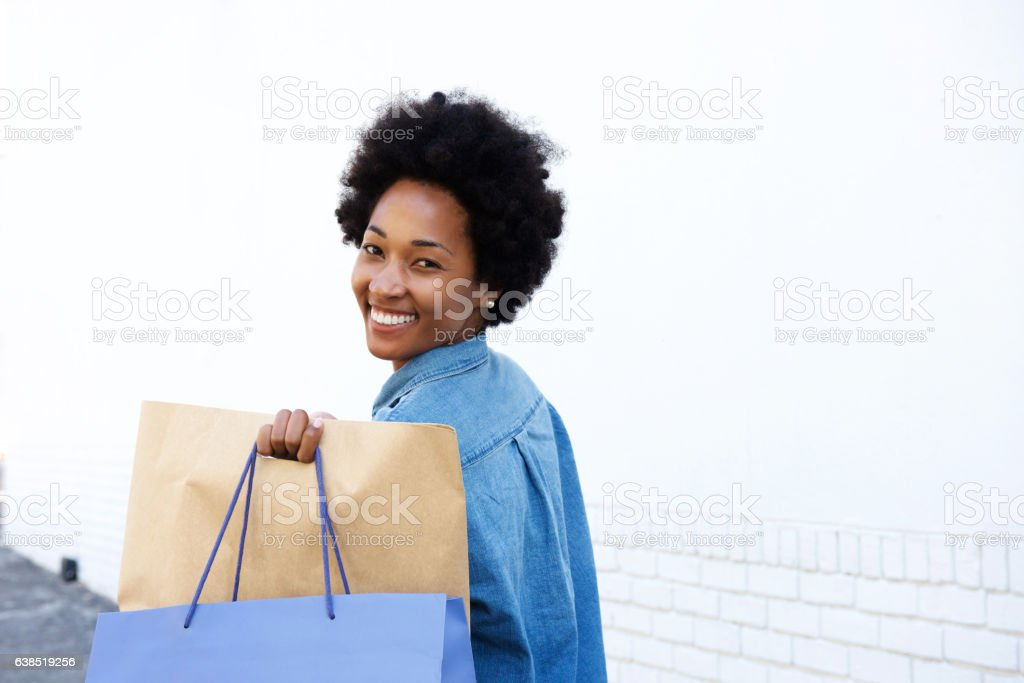 Happy woman walking with shopping on sidewalk stock photo