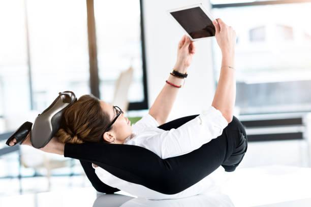 glückliche frau digitalgerät anzusehen - yoga fürs büro stock-fotos und bilder