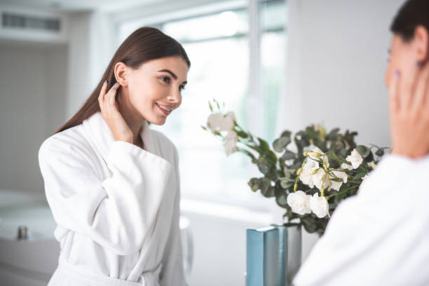 Happy woman watching at reflection in bathroom stock photo
