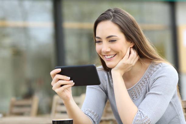 Happy woman watching video on phone in a coffee shop stock photo