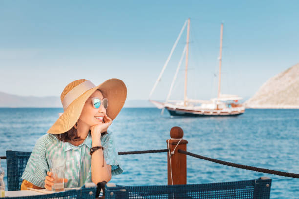 Happy woman wearing big hat sitting in cafe and looking to the seascape stock photo
