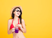 istock Happy woman wearing bikini and drinking  tropical cocktail 948490904