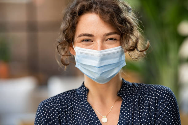 Happy woman wearing face mask stock photo