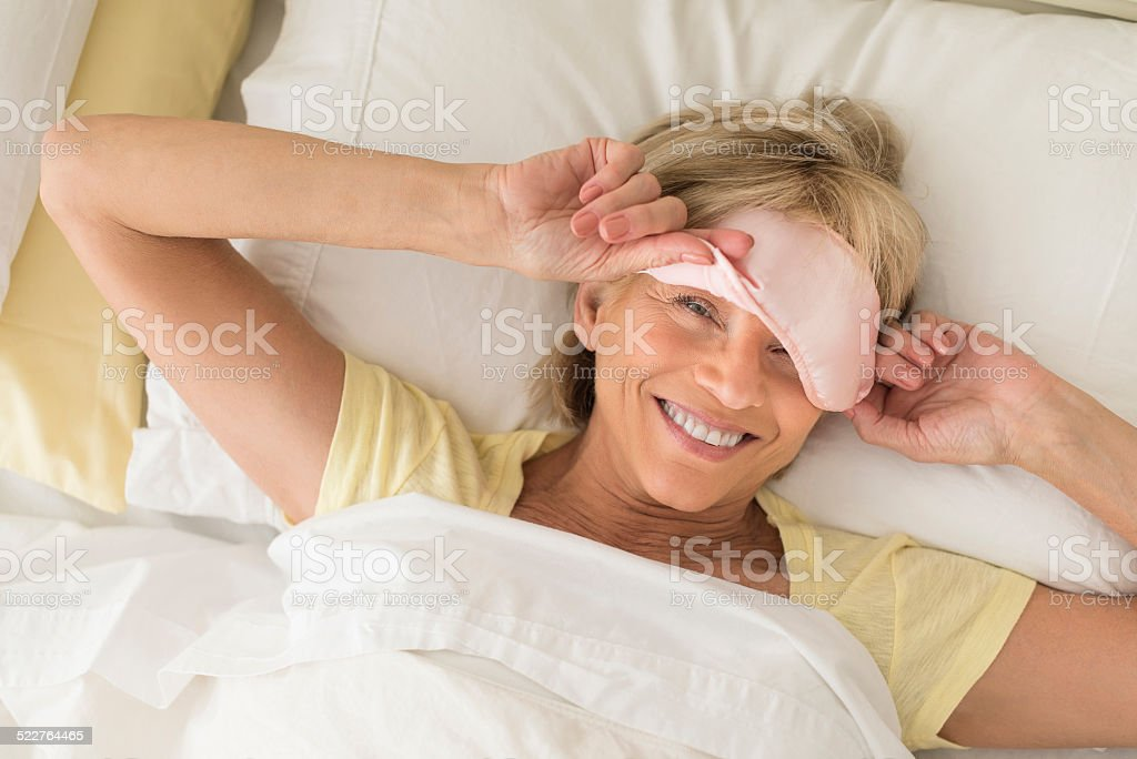 Happy Woman Wearing Sleep Mask On Bed stock photo