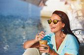 幸せな女のサングラス、アイス コーヒーのグラスを押しながら離れて笑顔を探して