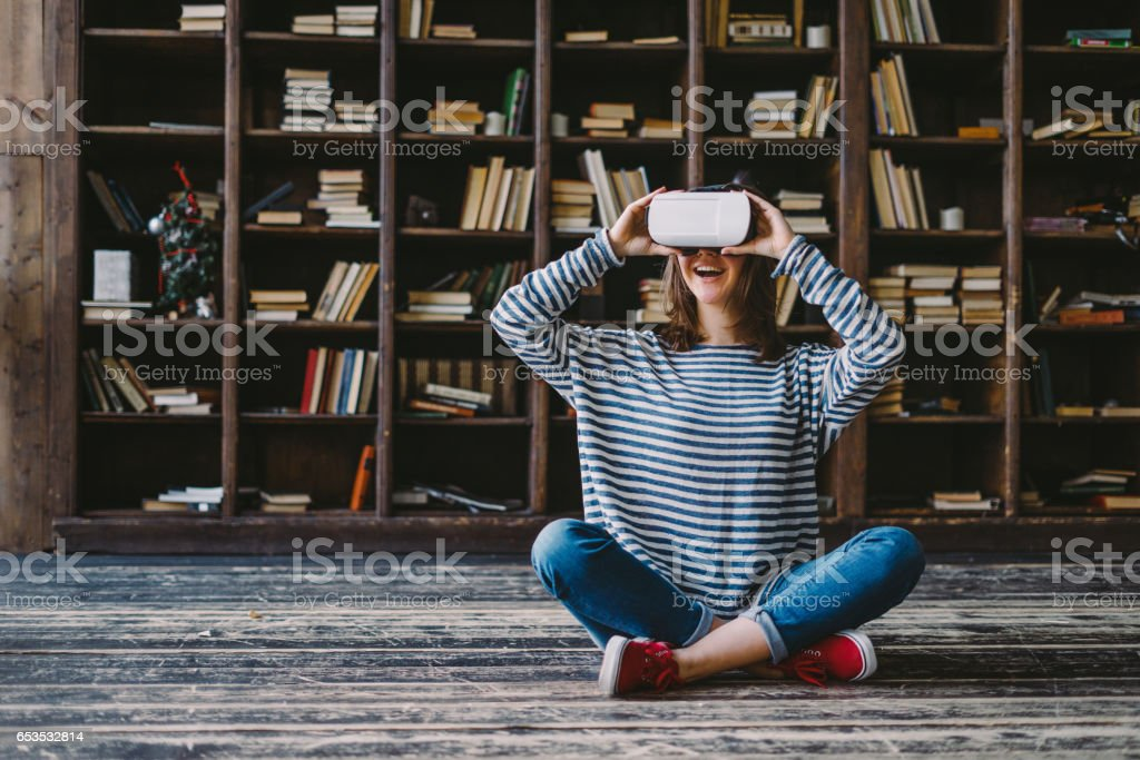 Happy woman wearing VR Glasses in front of bookshelves stock photo