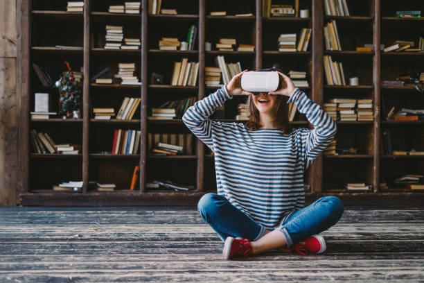 happy woman wearing vr glasses in front of bookshelves - mobile game stock photos and pictures