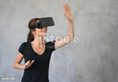 istock Happy woman wearing VR Glasses 544812434